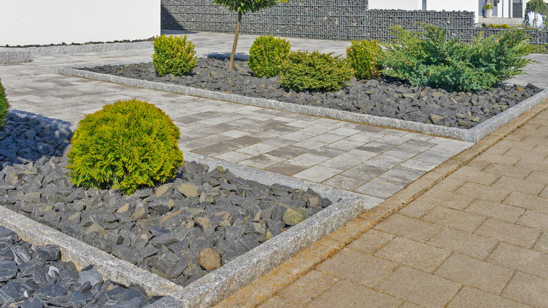 A paver side walk with decorative rock accents and small shrubs outside a commercial building in Bethlehem, %%sate%%.